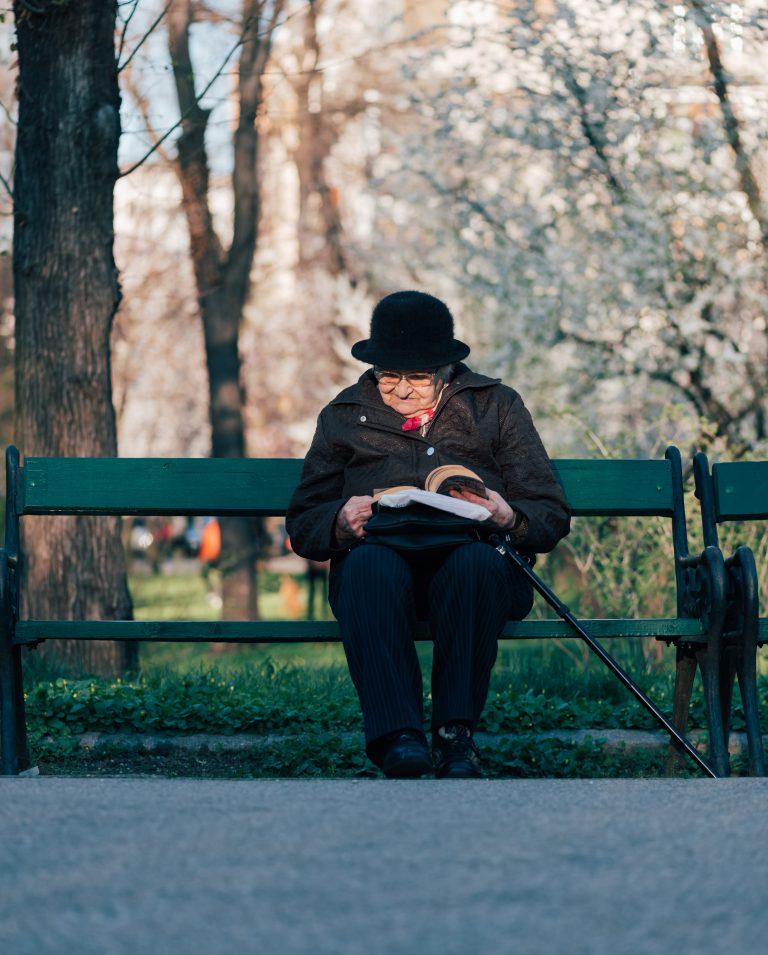 Alte Dame sitzt auf Parkbank und liest ein Buch